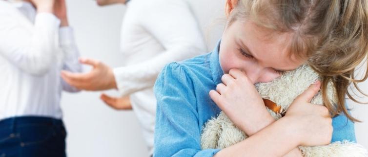 Forældre der skændes mens barn krammer sin bamse- skilsmisse og børn