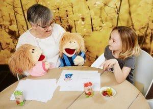 Bettina sidder og taler med et barn om familiens skilsmisse