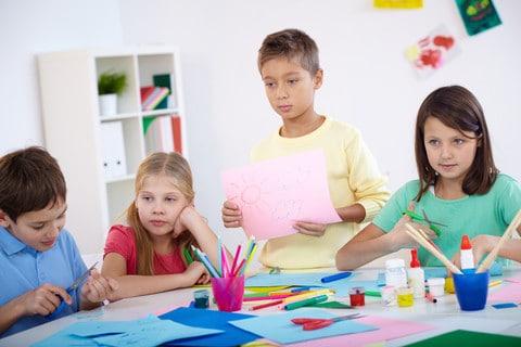 Billedet viser 4 børn, der er i gang med at løse en opgave de har fået i et børnegruppeforløb.