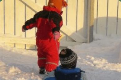 Boern der leger i sneen i vinterferien